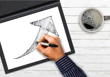 Auf einem Tablet zeichnet eine männliche Hand einen geschwungenen Pfeil fertig, daneben eine Kaffeetasse auf weißem Holztisch.
