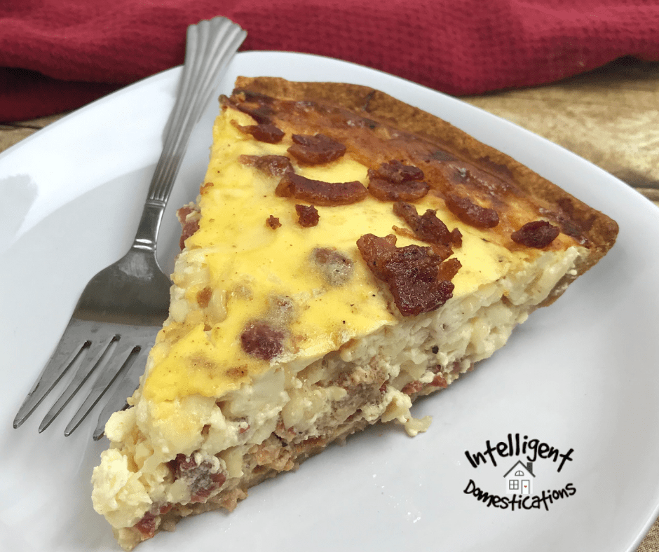 A slice of Bacon and Swiss Quiche on a white plate