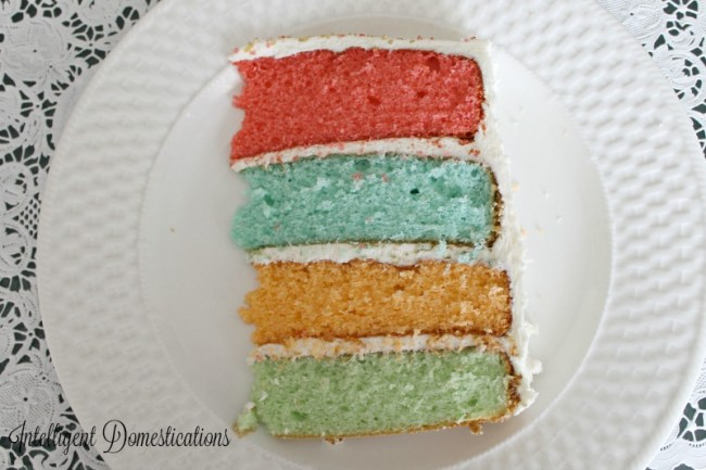 Rainbow layer cake slice fills up a dinner plate. You must make this cake at least once for your celebration.intelligentdomestications.com