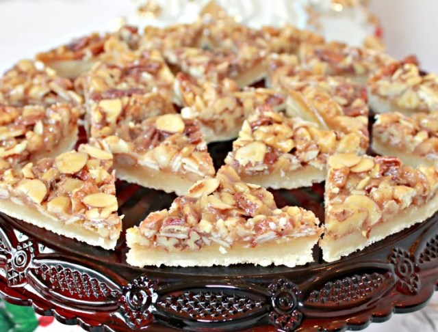 Nut bar cookies sliced into small triangles and served on a red cake plate