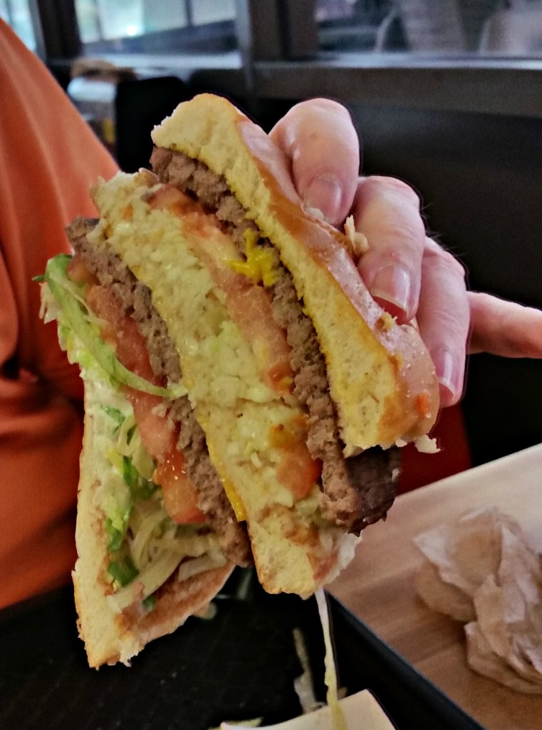 a very big double cheeseburger sliced in half