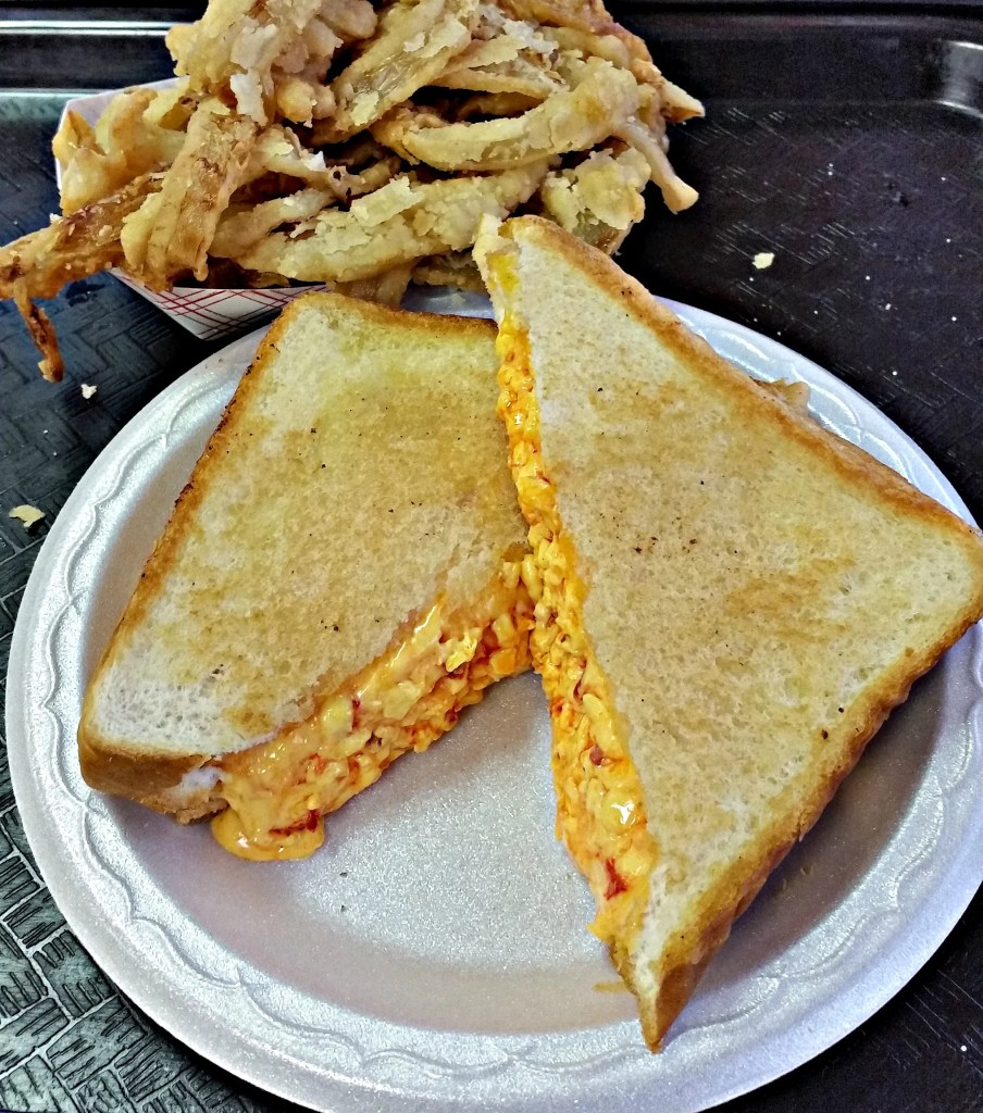 A Pimento Cheese Sandwich and fried onion rings on a paper plate