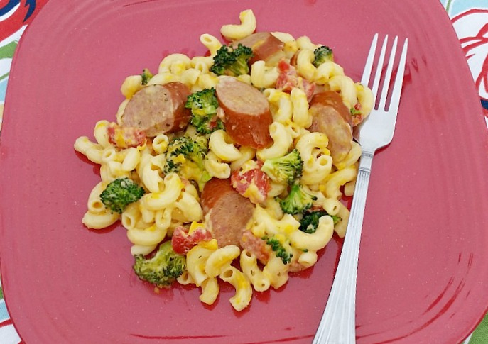 Broccoli and sausage with tomatoes in macaroni and cheese served on a red dish
