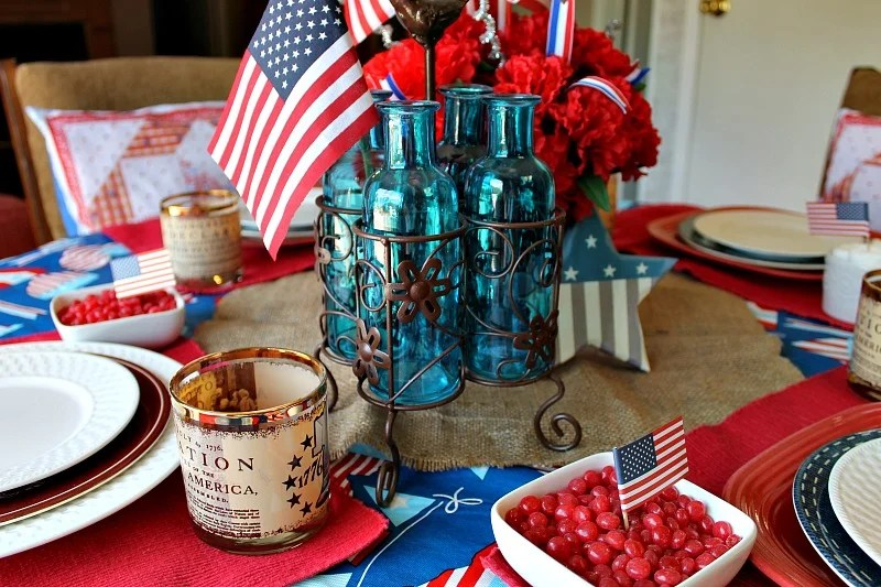 Blue bottles in their metal crate add a whimsical touch to my Patriotic tablescape. I stuck a flag inside one of the bottles. You can never have too many flags in a Patriotic tablescape