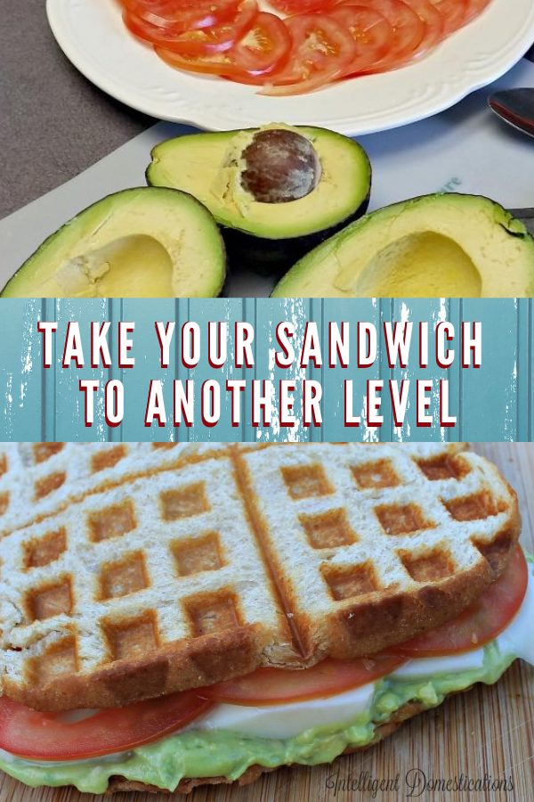 Sliced tomatoes and avocado cut open on a plate next to a sandwich grilled in the waffle iron