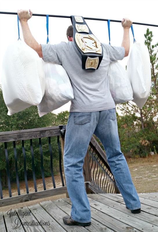 a man raising four bags of trash on a bar as if it's super heavy