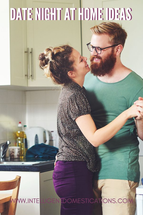 A Couple slow dancing in their kitchen for a date at home event.
