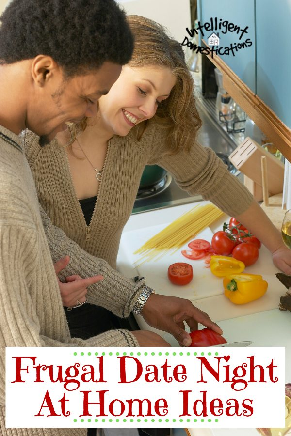 A couple cooking a meal together in their kitchen. He is chopping tomatoes while she looks on. Ingredients on the counter suggest they are making homemade spaghetti