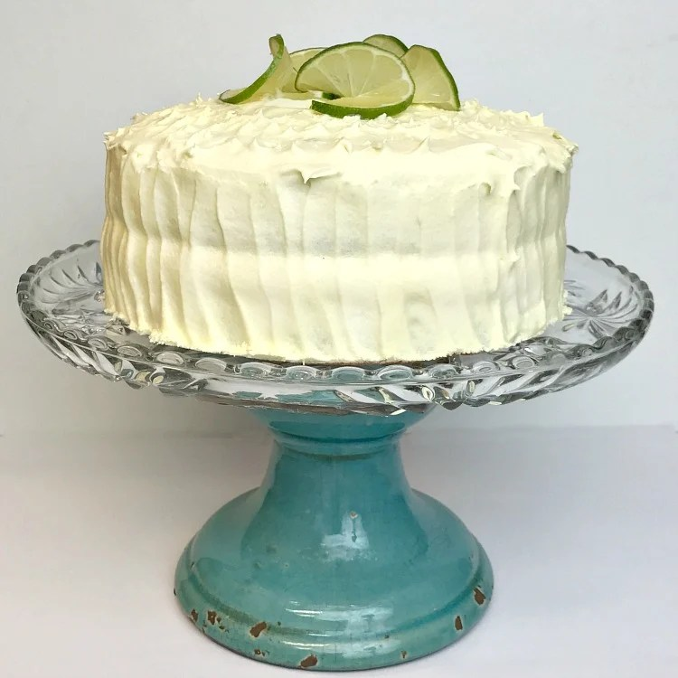 a two layer cake frosted with lime slices on top  displayed on a cake plate on a stand
