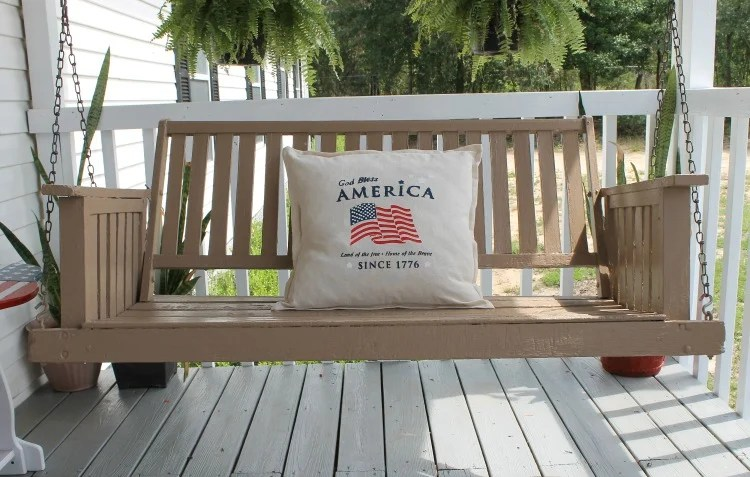 Porch-swing-makeover-After-picture.-Painted-with-DecoArt-Pergola-with-DIY-God-Bless-America-stenciled-pillow