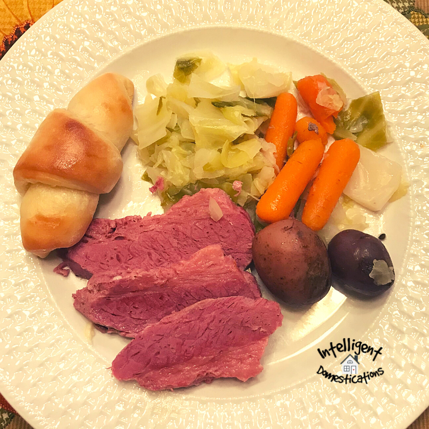 A dinner plate with Corned Beef, Cabbage, Carrots and Potatoes with a roll