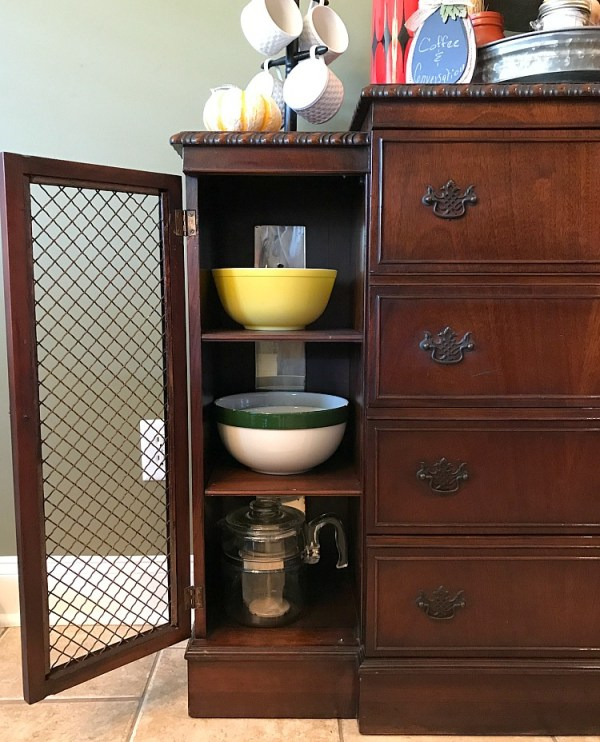 A peep inside an antique dining room sideboard filled with vintage bowls