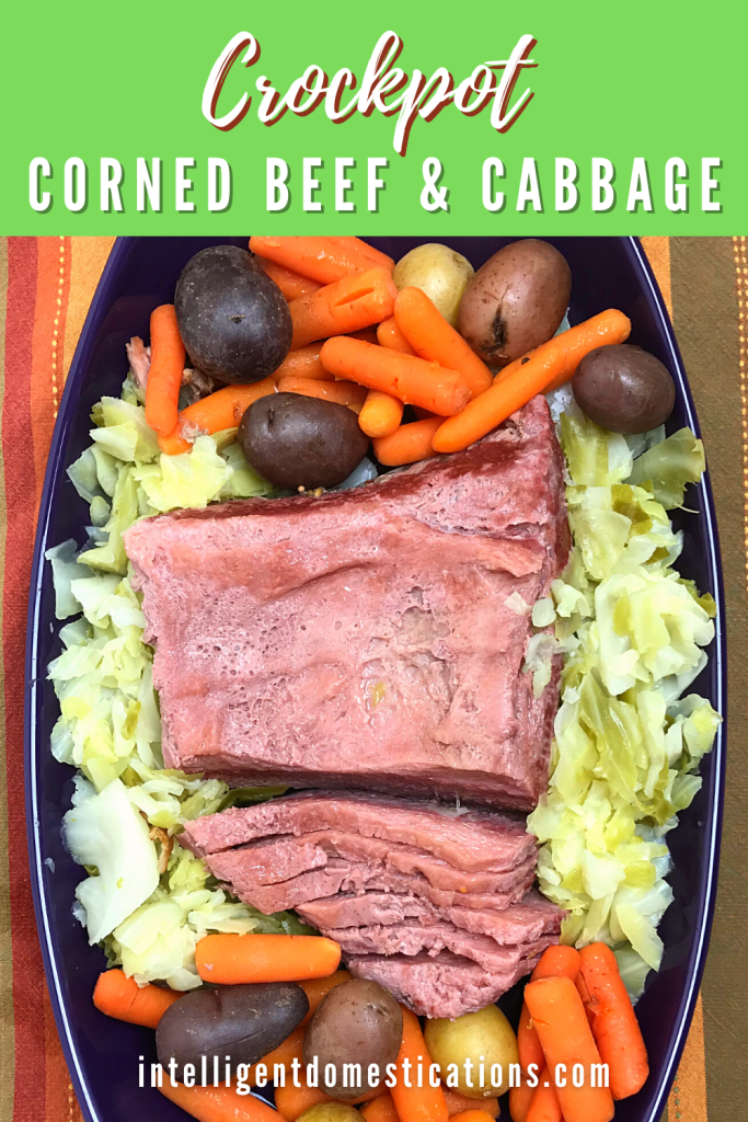 Cooked Corned beef brisket, cabbage, carrots and potatoes in a purple serving dish on a table