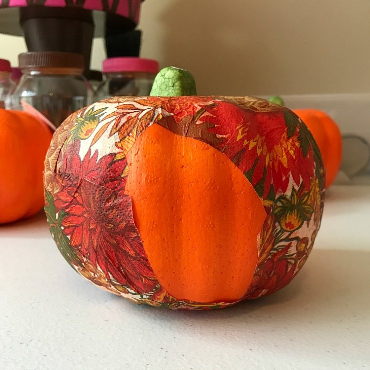 Fall Napkin being glued onto a Dollar Store Pumpkin with just one spot left to cover