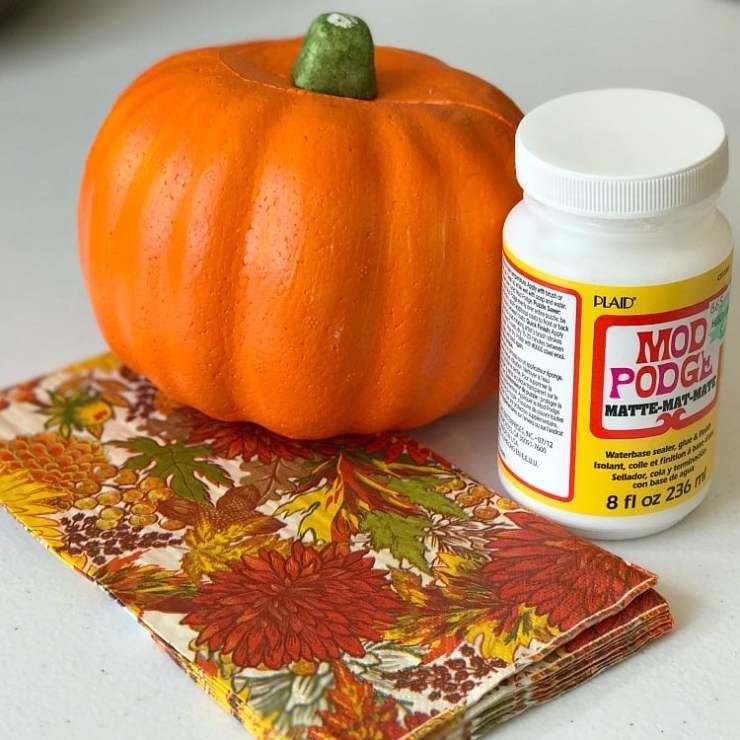 Fall napkins, a dollar store orange pumpkin and Mod Podge decoupage glue all on a white background