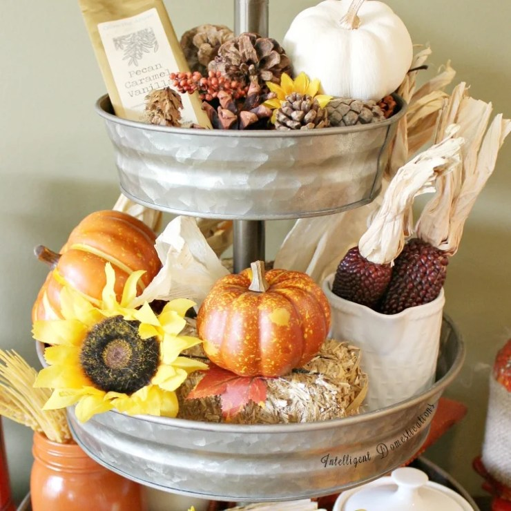 Top two tiers of a galvanized three tier tray decorated for fall with pumpkins, flowers, pine cones and dried corn