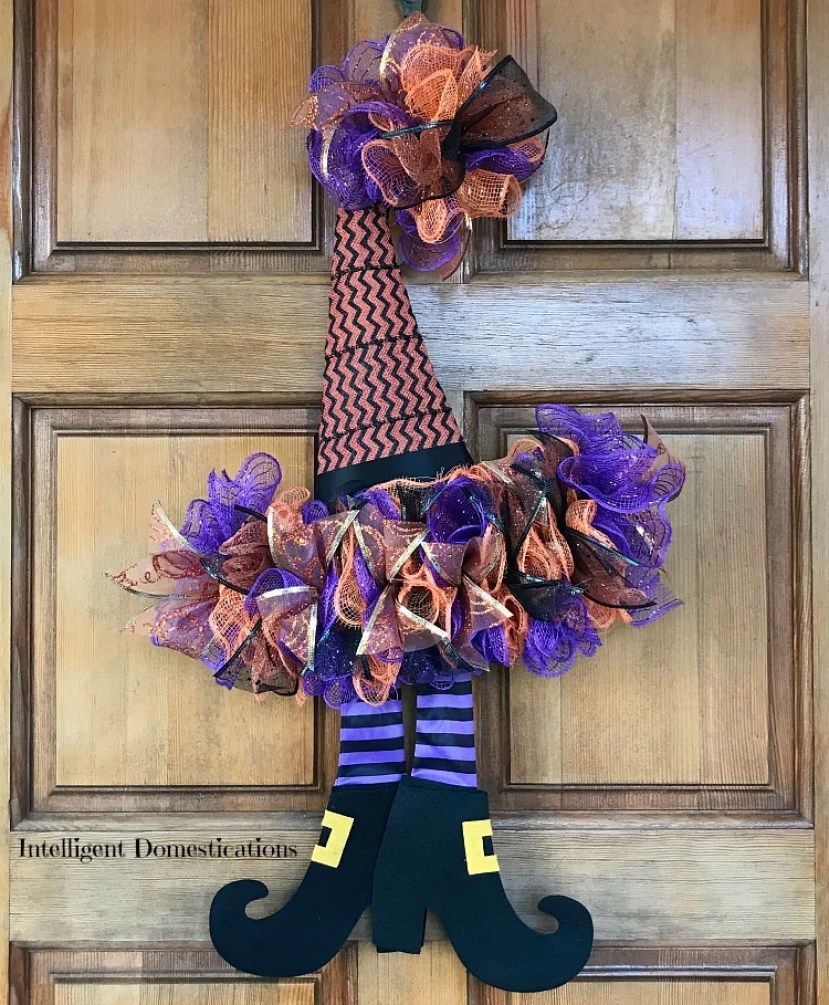 A whimsical purple and orange Witches hat wreath hanging on a front door