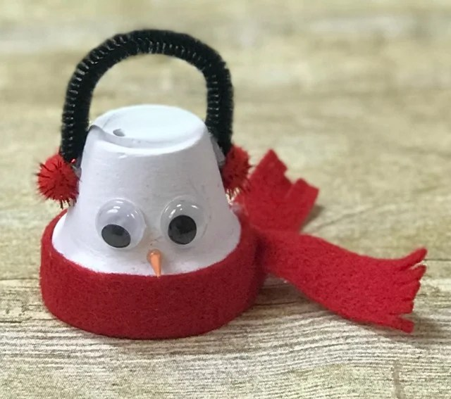 a snowman Christmas ornament made from a clay pot and felt with googly eyes