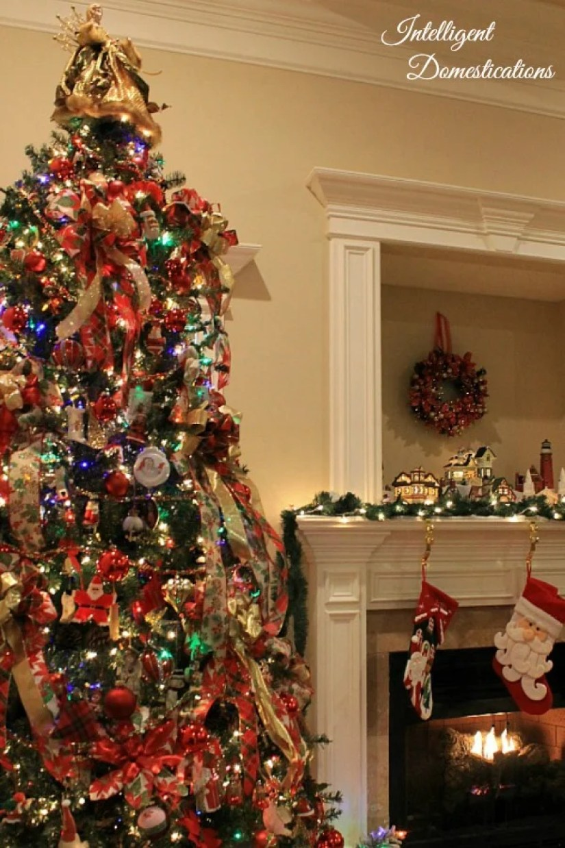 A tall Christmas tree decorated with red and gold ribbons, bows and ornaments