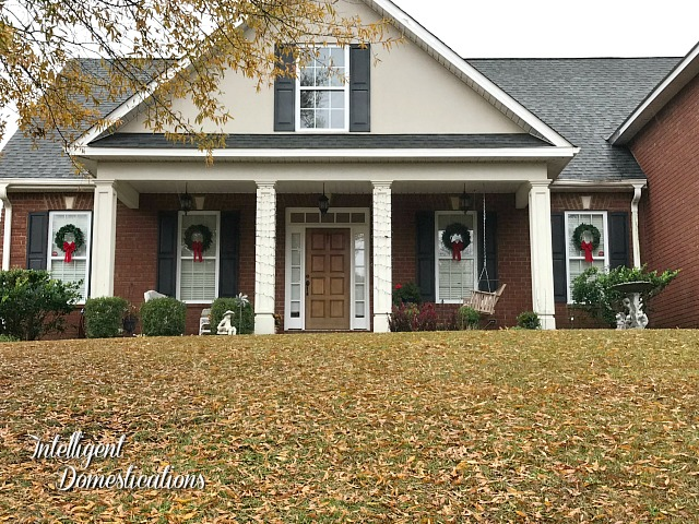 a brick house with Christmas wreaths with red bows hung on outside windows