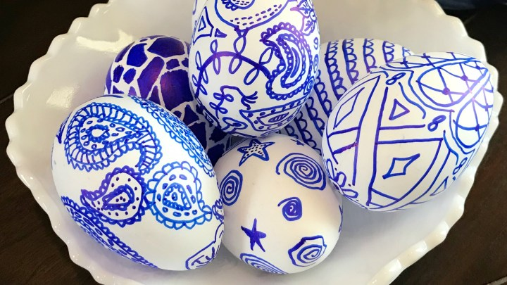 Blue and white paisley Easter eggs displayed in a white bowl on a table