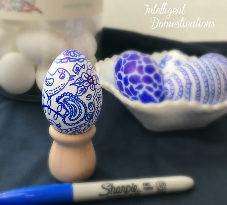 a hand drawn decorated Easter Egg in blue and white with paisley and a bird displayed in a wood holder