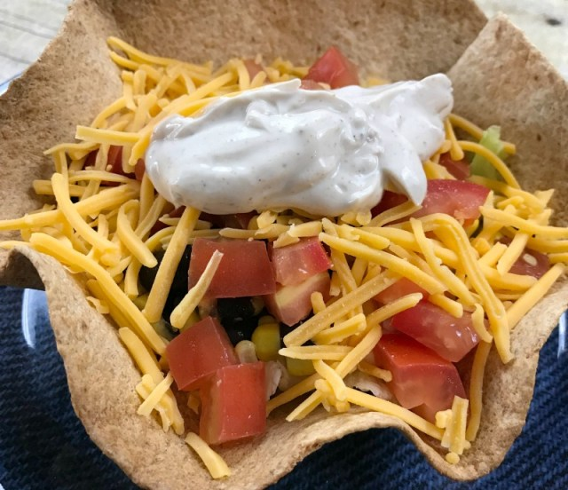 Meatless Taco Salad served in a Homemade Tortilla Bowl. So much flavor with seasoned Sour Cream Dressing, Black Beans, Corn and Roma tomatoes. #tacosalad #tacotuesday