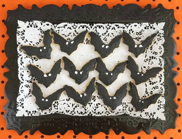 Decorated Bat Sugar Cookies for Halloween on a black tray lined with white paper sitting on an orange table cover