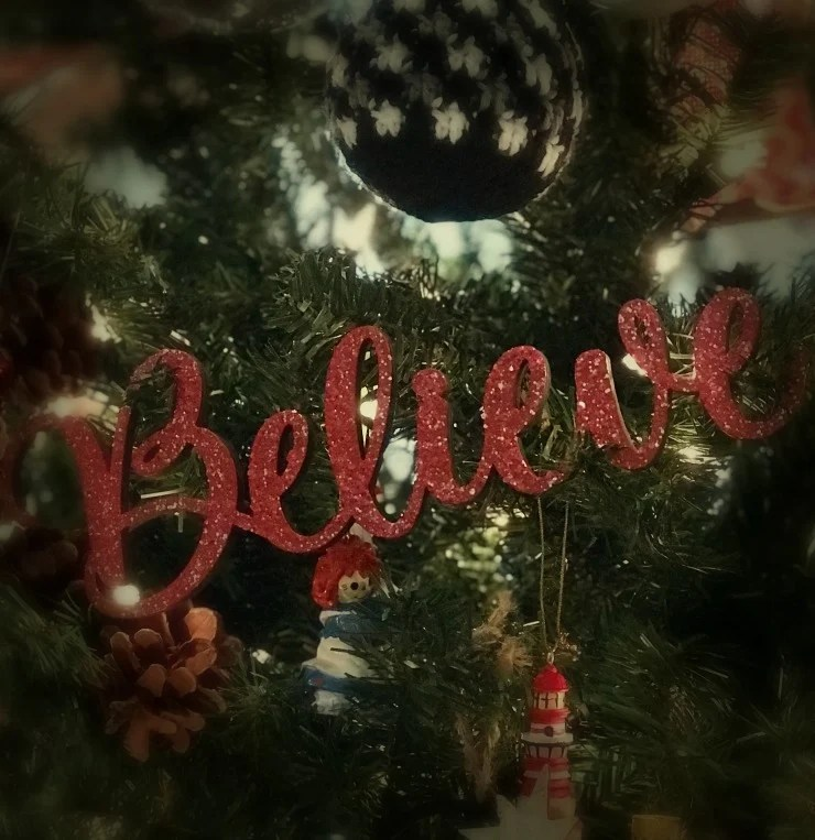 Wood BELIEVE Christmas ornament painted with red glitter paint hanging on a Christmas tree