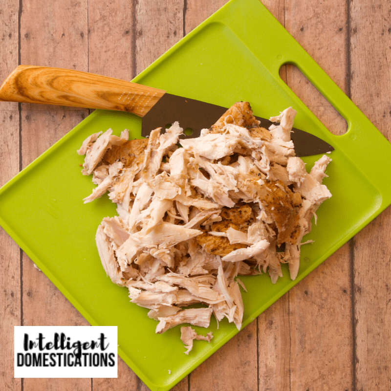 Chopped Rotisserie Chicken on a cutting board next to a knife