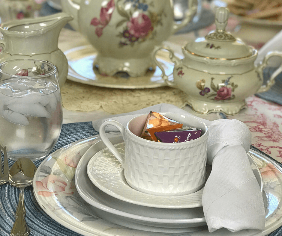 Spring Tea Tablescape Ideas using pretty floral dishes and pastel colors along with light refreshments. #springtablescape #intellid