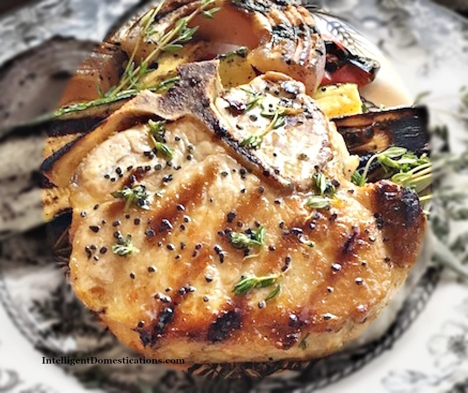 Grilled Pork Chops rubbed with fresh herbs. Bone in. Easy summer grilling recipe for a quick weeknight meal. #grilledporkchops #porkchops #summergrilling