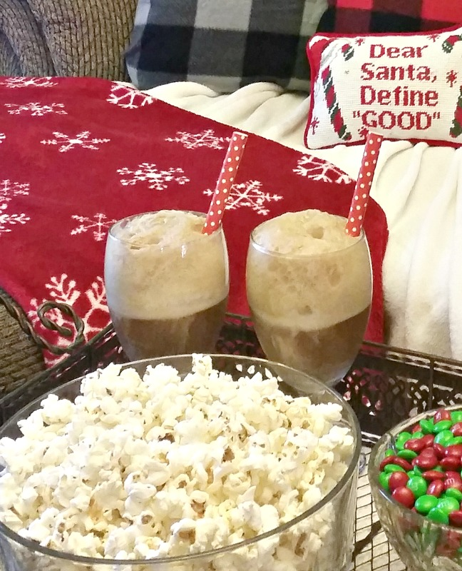 Coke floats in stemmed glasses on a tray with popcorn in a bowl and M&M candies also in a bowl. The tray is sitting next to a sofa with red Christmas blankets