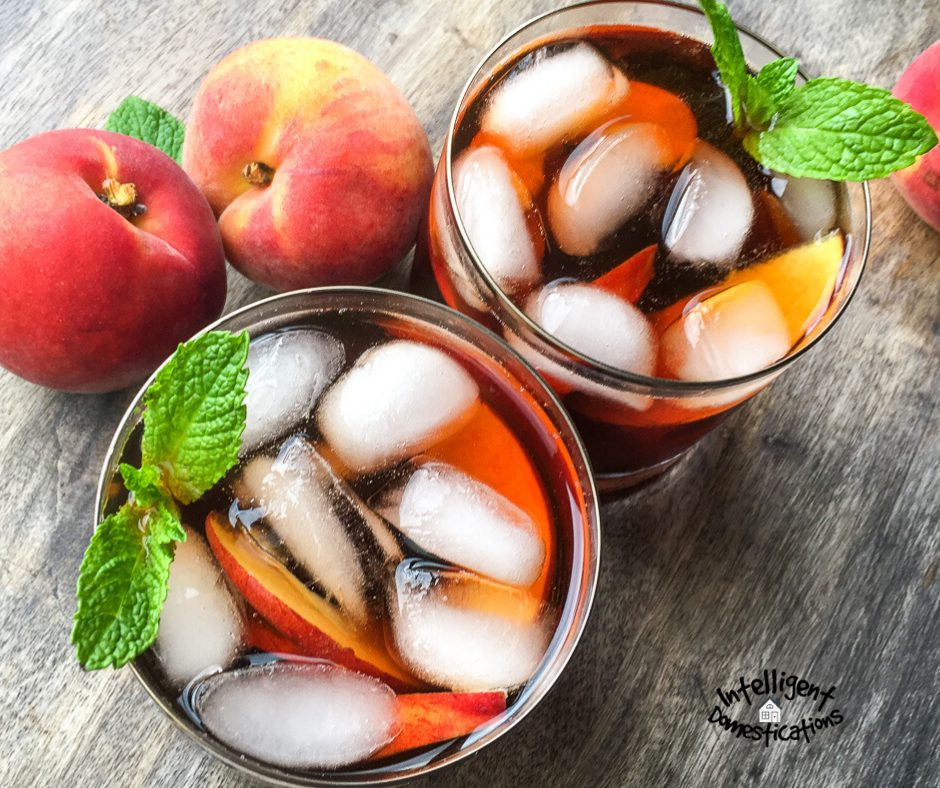 Two glasses of iced tea viewed from above with peach slices among the ice and whole peaches displayed next to the glasses on a wood surface
