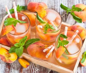 A wood tray filled with glasses of Peach iced tea and sliced peaches with mint sprigs on a wood table