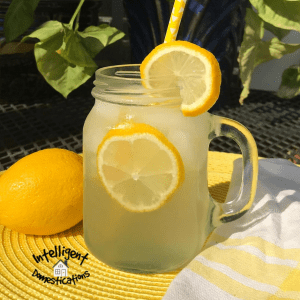 A Mason jar filled with lemonade with lemons floating in it on a yellow place mat in an outdoor dining setting