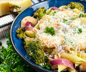 Pasta meal with shrimp and broccoli in a blue bowl