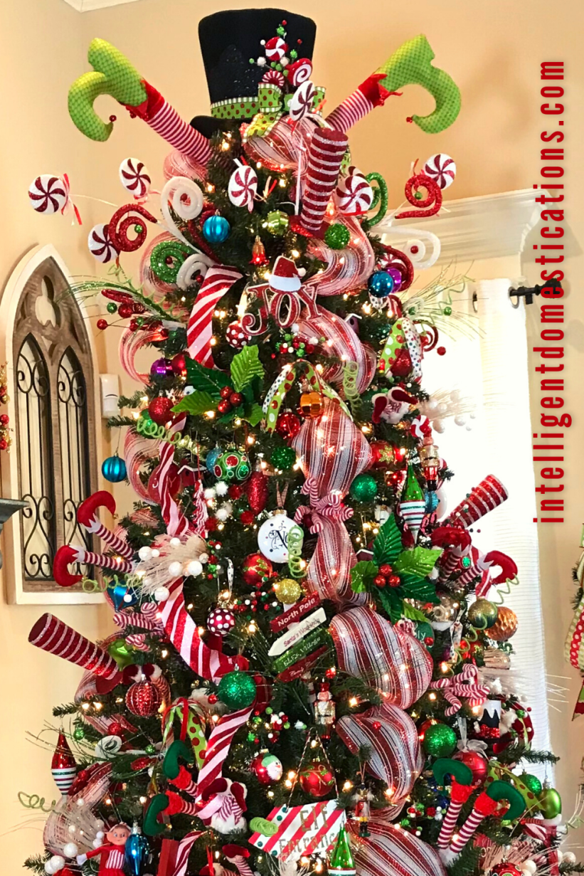 A Christmas tree decorated in bright red and green colors with whimsical Elves