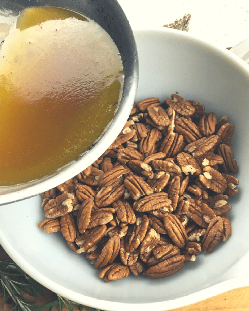 Pouring a spice mixture over pecan halves in a bowl