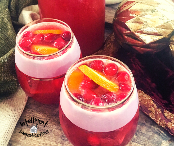 Christmas punch served in small glass with cranberries and and orange slice on top