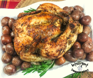 oven roasted chicken and red potatoes on a white platter with sprigs of thyme