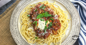 Chicken Parmesan on a bed of spaghetti with chopped Basil on top served on a white dish