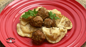 Pierogi's and meatballs on a red dish with alfredo sauce