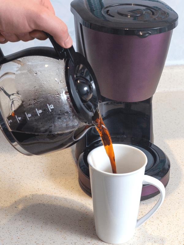 pouring hot coffee into a white mug