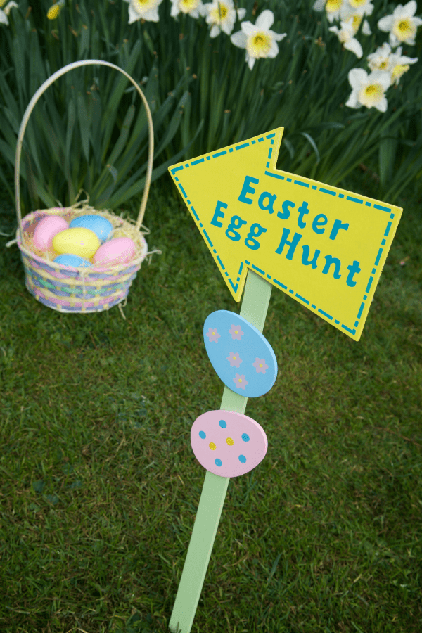An Easter Egg Hunt sign in the grass next to an Easter basket with plastic eggs