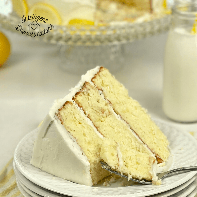 a piece of three layer lemon cake on a plate in front of the cake stand and a bottle of milk