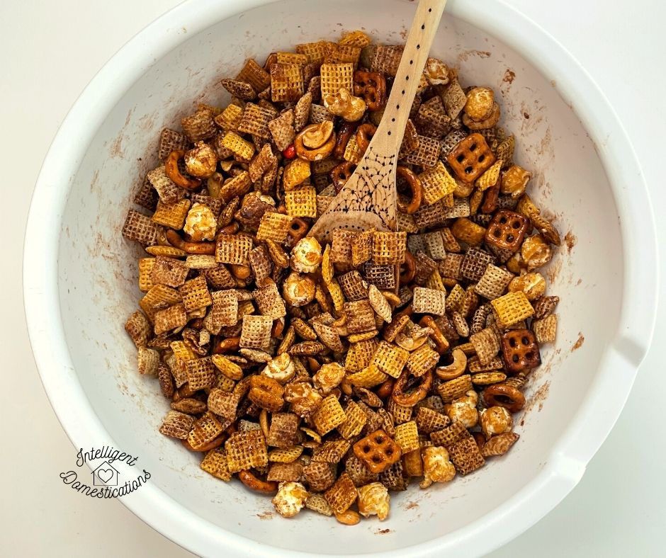 Pumpkin spice Chex mix being blended with seasoning in white bowl
