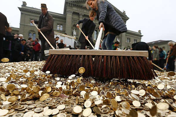 Supporters of Generation Basic Income sweep away Swiss coins in Bern. The group just filed a referendum to Swiss voters guaranteeing Swiss adults a basic income. (Image Source: Reuters)