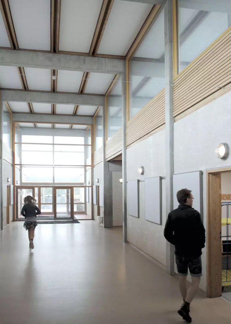 Girl walking down architect drawn hallway at Skovly Skolen with acoustic ceiling and acoustic bulletin boards in frames. All acoustic products made by Intelligent Space (INSP)