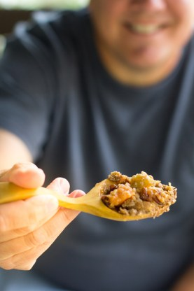 image of a man holding a wooden spoon full of the best ever sweet potato casserole recipe by intentionally eat